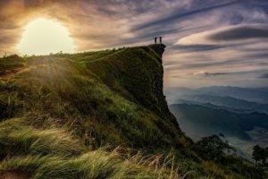 Zwei Personen, die an einer Klippe stehe und der Sonne zugewandt ihre Hände in den Himmel strecken.