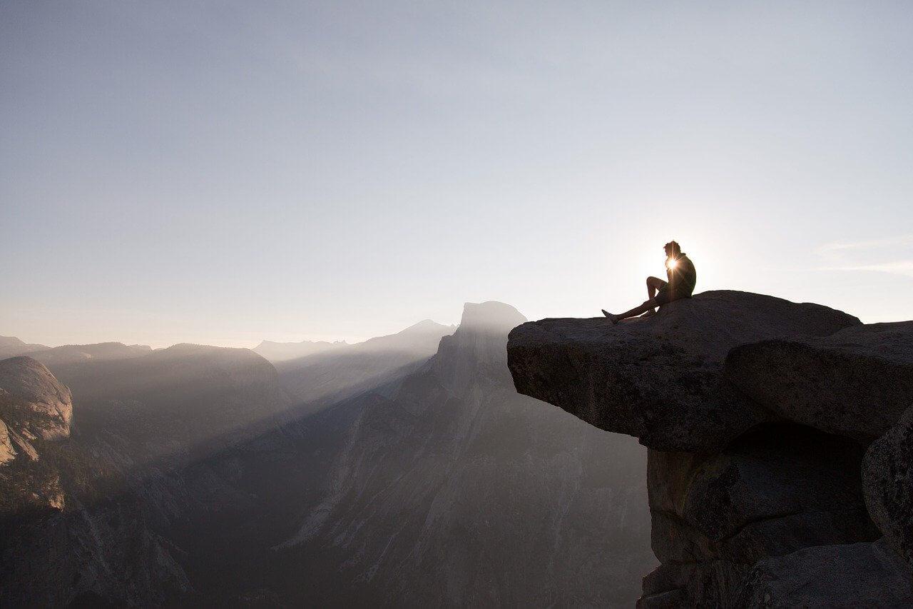 Ein Mann der auf einer Klippe sitzt und den Sonnenaufgang genießt. Er hat seinen Beruf gefunden.