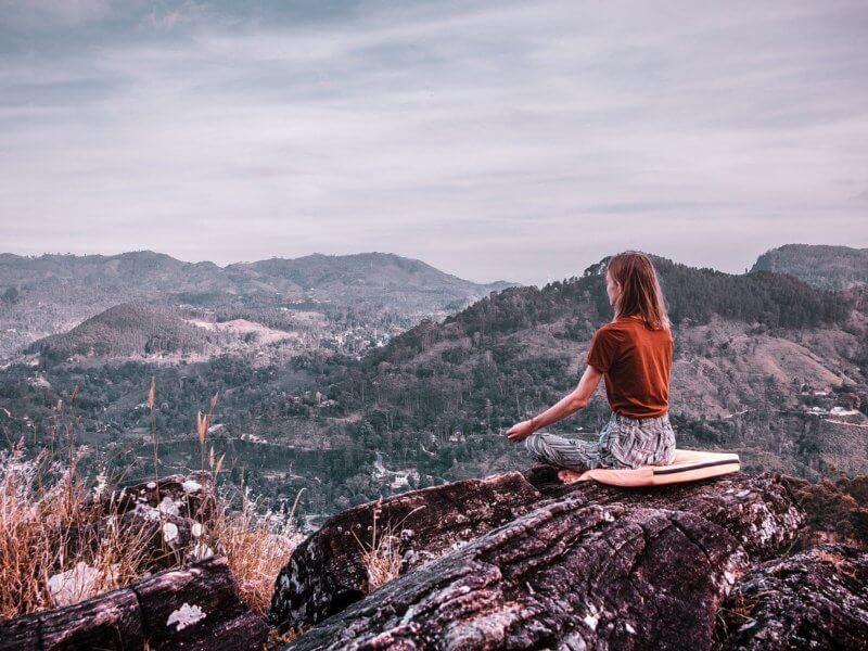 Selbstverwirklichung durch Meditieren. Frau sitzt in den Bergen und meditiert.
